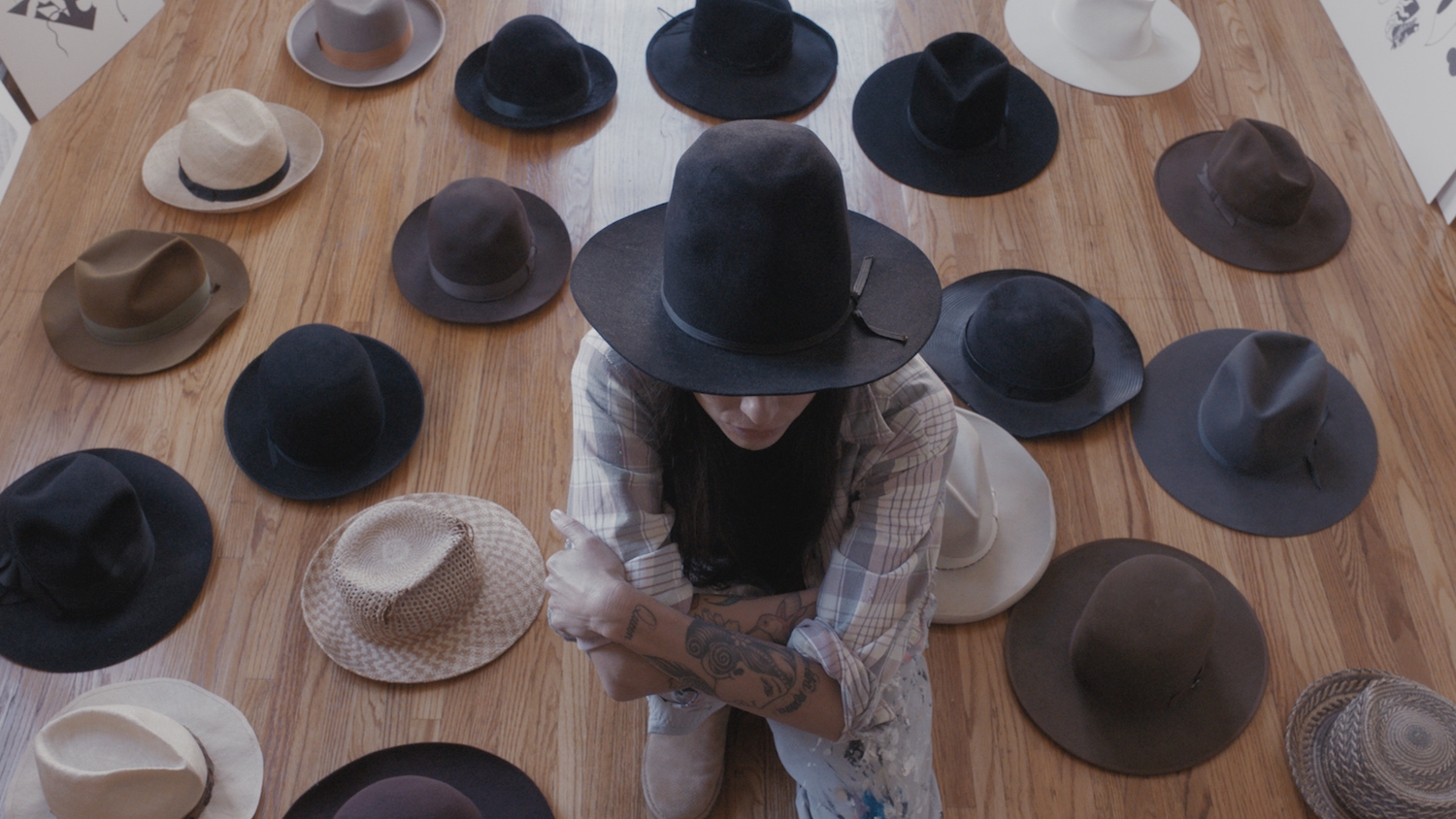 The artist sits among her impressive collection of hats.