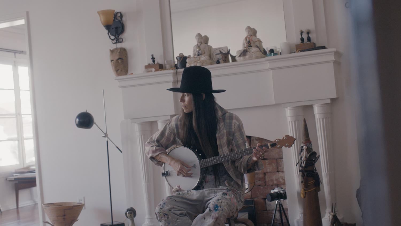 Tasya plays the banjo in her living room.