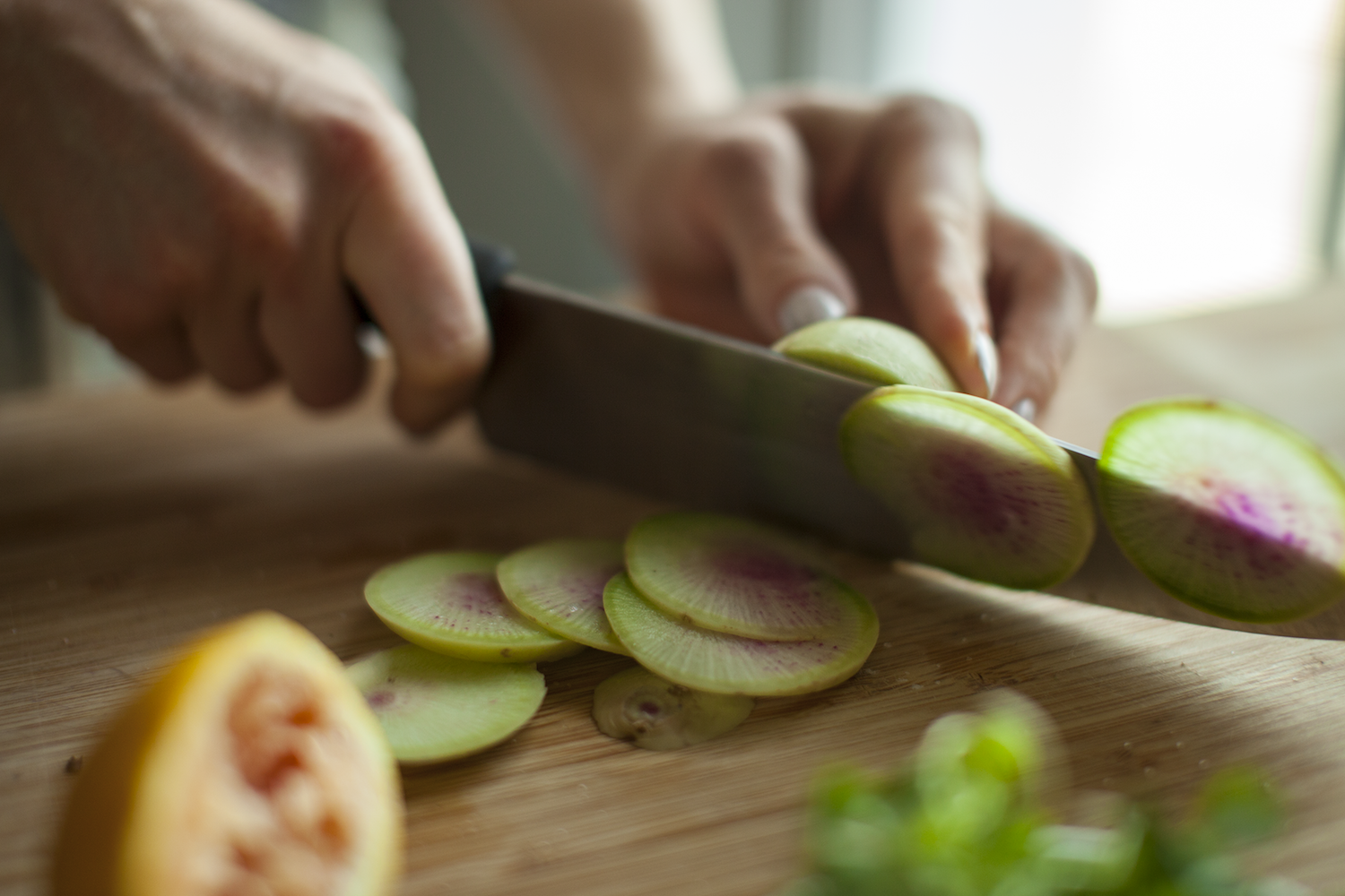 Lee thinly slices a watermelon radish
