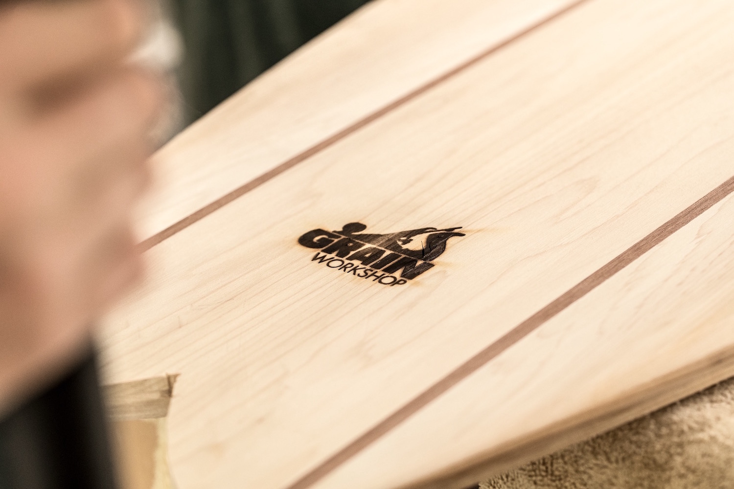 A surfboard freshly branded with the Grain Workshop logo