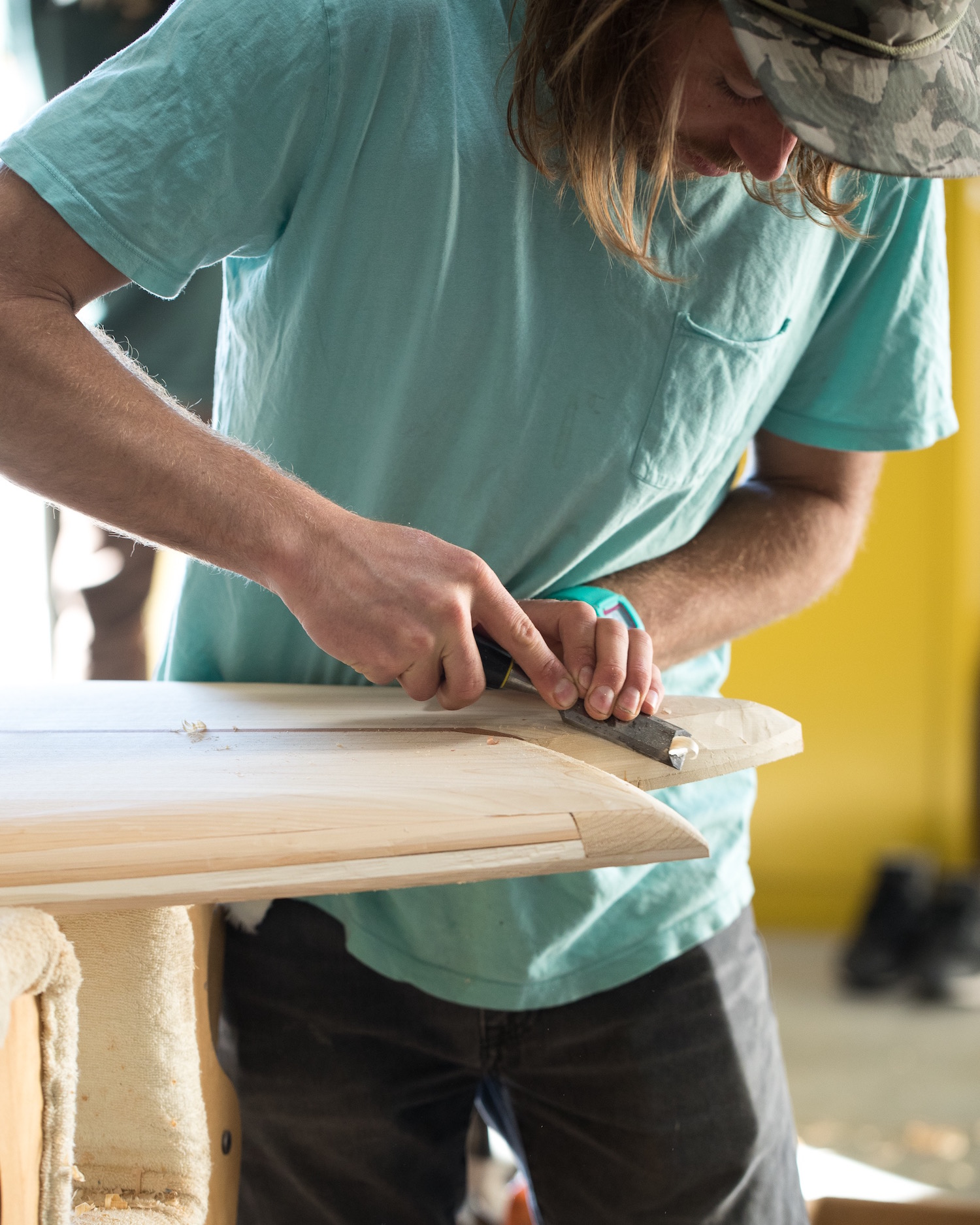 Nolan Collins helps shape the tail of a surfboard with a chisel.