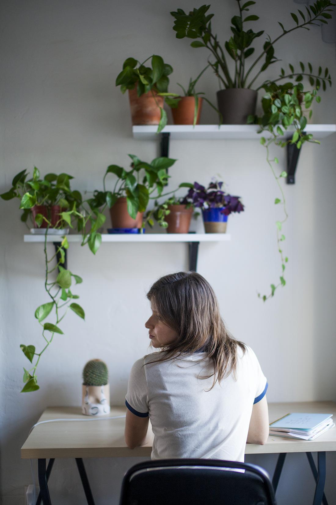 Lee sits at her desk below shelves of plants.