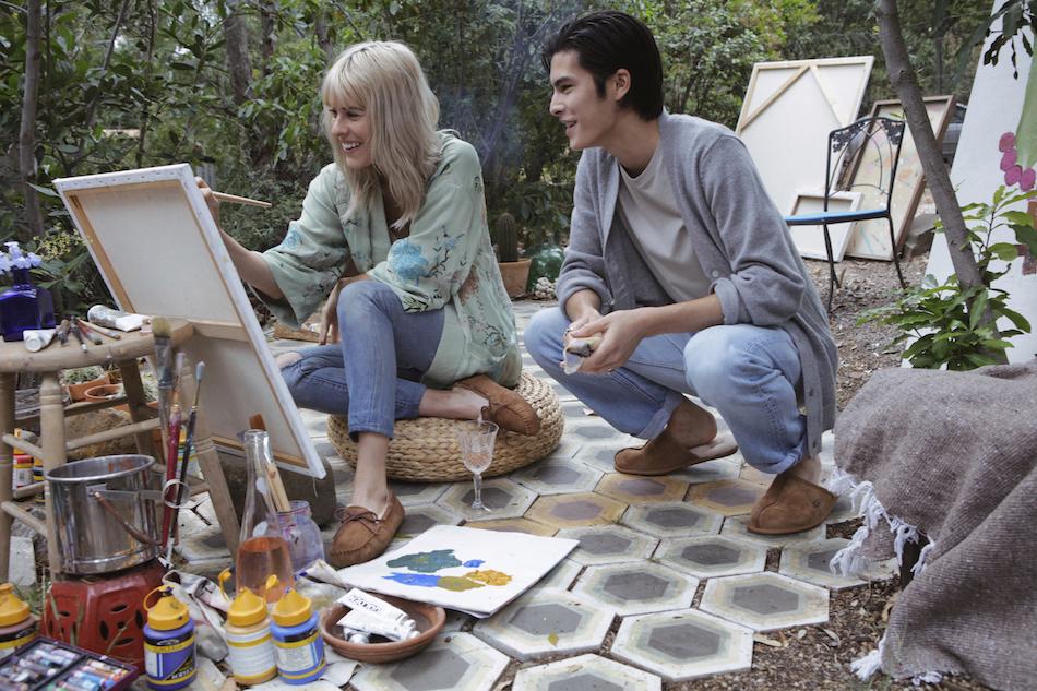 Female model wearing the Dakota slipper smiles and paints while male model wearing the Scuff slipper happily observes