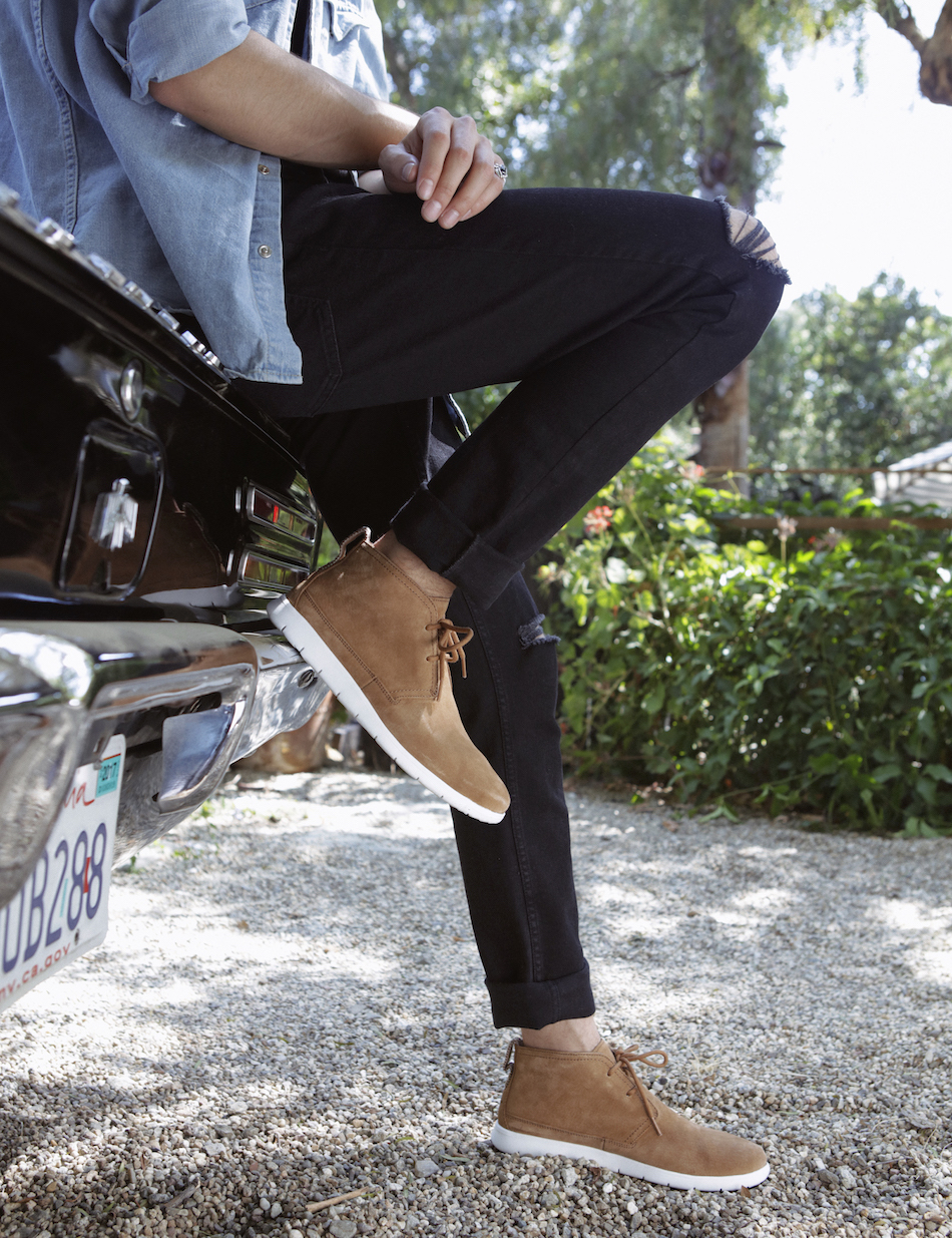 Model wears the Freamon in Chestnut while resting on the trunk of a car.