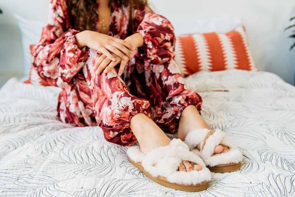Model wears a floral silk pajama set and the Abela in Natural while lounging in bed.